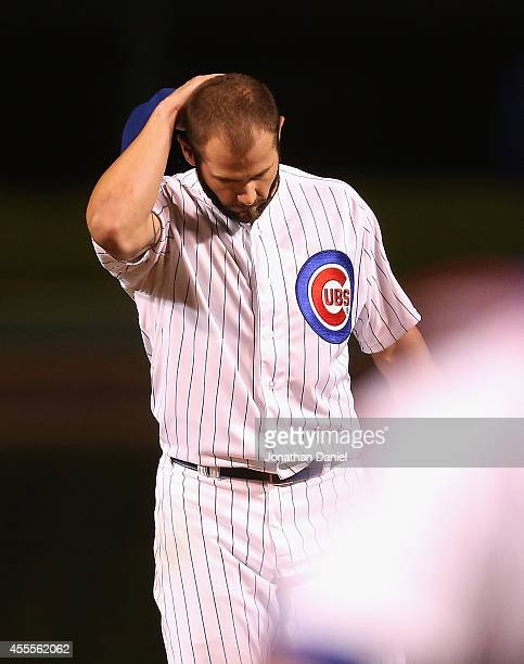 Starting pitcher Jake Arrieta of the Chicago Cubs reacts after giving up a double in the 8th inning to Brandon Phillips of the Cincinnati Reds to end...