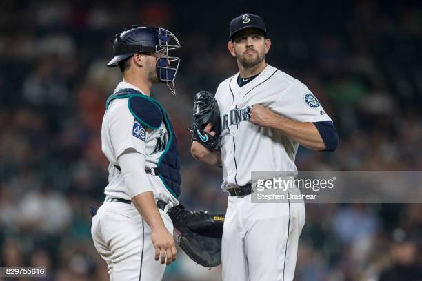 Starting pitcher James Paxton of the Seattle Mariners grabs his jersey while meeting at the pitcher's mound with catcher Mike Zunino of the Seattle...