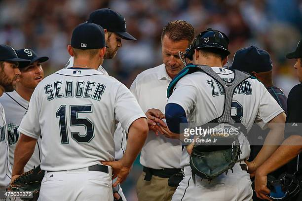 Starting pitcher James Paxton of the Seattle Mariners has his hand examined by trainer Rob Nodine prior to being removed from the game due to injury...