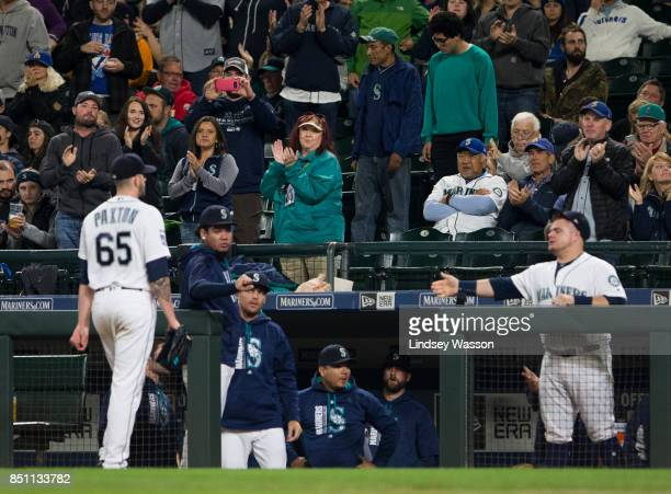 Starting pitcher James Paxton of the Seattle Mariners is applauded by fans as he returns to the dugout after being replaced by Dan Altavilla in the...