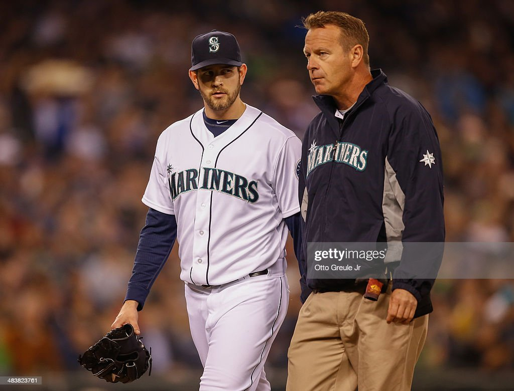 Starting pitcher James Paxton #65 of the Seattle Mariners is escorted off the field by assistant trainer Rob Nodine in the sixth inning against the Los Angeles Angels of Anaheim on Opening Day at Safeco Field on April 8, 2014 in Seattle, Washington.
