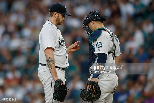 Starting pitcher James Paxton of the Seattle Mariners pauses on the mound to look at his hand prior to being removed from the game due to injury in...