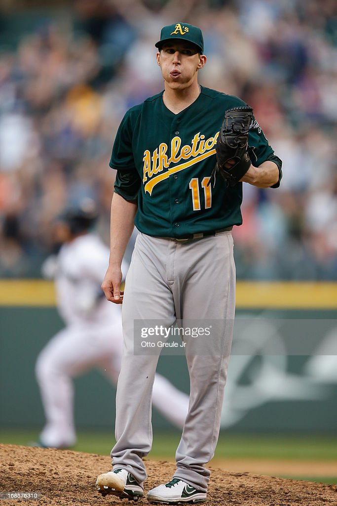 Starting pitcher <a gi-track='captionPersonalityLinkClicked' href=/galleries/search?phrase=Jarrod+Parker&family=editorial&specificpeople=5970942 ng-click='$event.stopPropagation()'>Jarrod Parker</a> #11 of the Oakland Athletics reacts after giving up a two-run homer to Kelly Shoppach of the Seattle Mariners in the fifth inning at Safeco Field on May 11, 2013 in Seattle, Washington. The homer broke up a no-hitter.
