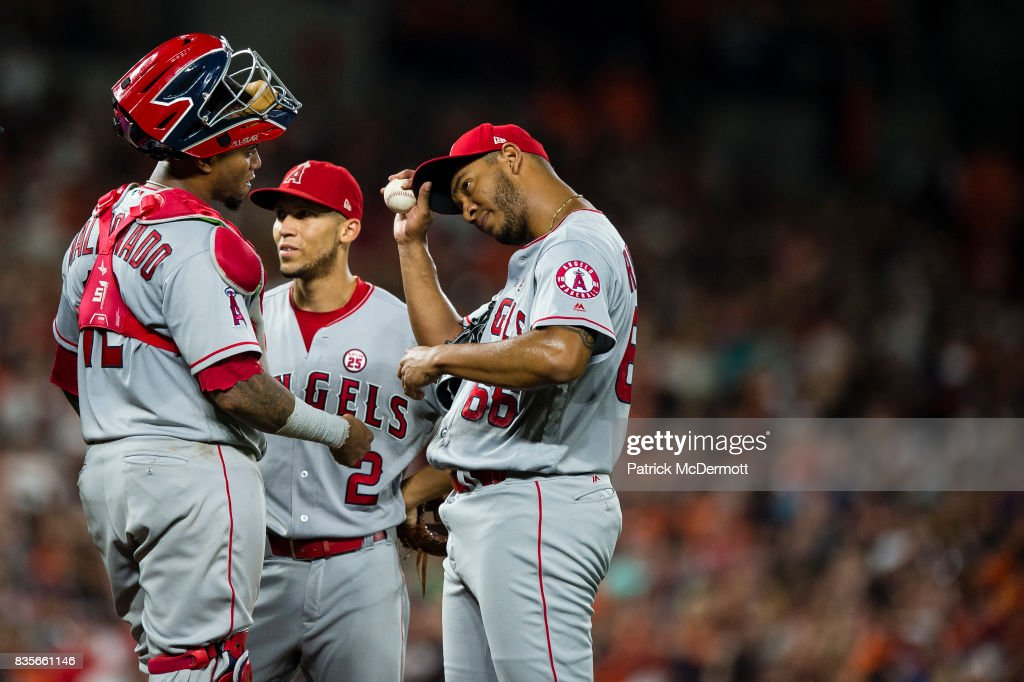 Starting pitcher JC Ramirez #66 of the Los Angeles Angels of Anaheim talks with Martin Maldonado #12 and Andrelton Simmons #2 before leaving the game with an injury in the sixth inning against the Baltimore Orioles at Oriole Park at Camden Yards on August 19, 2017 in Baltimore, Maryland.