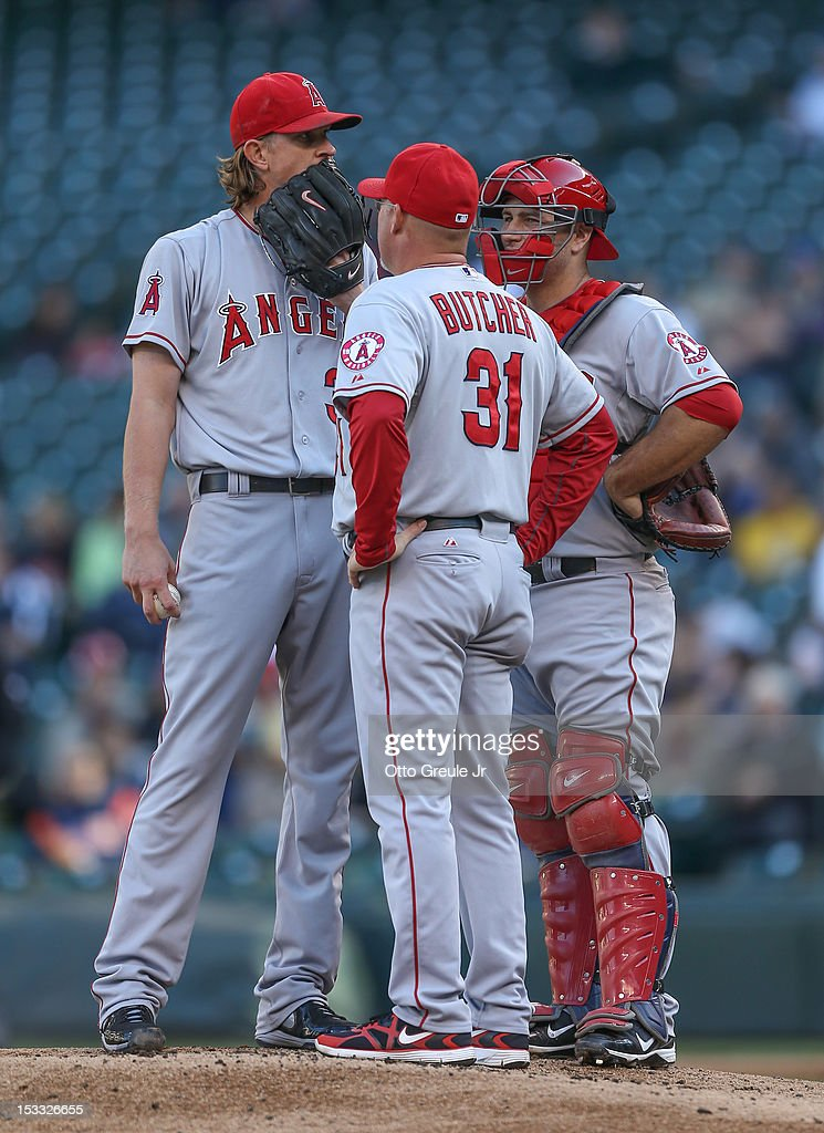 Starting pitcher <a gi-track='captionPersonalityLinkClicked' href=/galleries/search?phrase=Jered+Weaver&family=editorial&specificpeople=565100 ng-click='$event.stopPropagation()'>Jered Weaver</a> #36 of the Los Angeles Angels of Anaheim gets a visit from pitching coach Mike Butcher #31 in the first inning against the Seattle Mariners at Safeco Field on October 3, 2012 in Seattle, Washington. Weaver was removed from the game in the second inning.