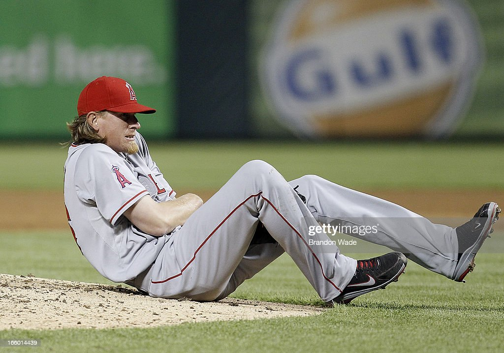 Starting pitcher <a gi-track='captionPersonalityLinkClicked' href=/galleries/search?phrase=Jered+Weaver&family=editorial&specificpeople=565100 ng-click='$event.stopPropagation()'>Jered Weaver</a> #36 of the Los Angeles Angels of Anaheim grabs his left elbow after falling awkwardly to avoid a line drive in the sixth inning of a baseball game against the Texas Rangers at Rangers Ballpark in Arlington on April 7, 2013 in Arlington, Texas. Texas won 7-3.