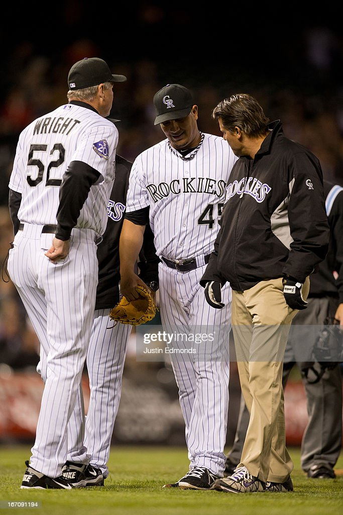 Starting pitcher <a gi-track='captionPersonalityLinkClicked' href=/galleries/search?phrase=Jhoulys+Chacin&family=editorial&specificpeople=5734320 ng-click='$event.stopPropagation()'>Jhoulys Chacin</a> #45 of the Colorado Rockies walks off the field under the watchful eye of pitching coach Jim Wright #52 and the trainer during the seventh inning against the Arizona Diamondbacks at Coors Field on April 19, 2013 in Denver, Colorado. The Rockies defeated the Diamondbacks 3-1.