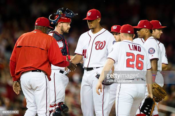 Starting pitcher Joe Ross of the Washington Nationals shakes hands with manager Dusty Baker after he is relieved in the eighth inning during a game...