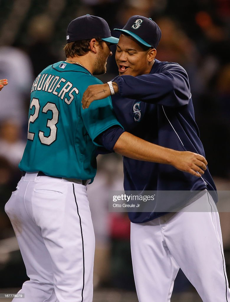 Starting pitcher Joe Saunders #23 (L) of the Seattle Mariners gets a hug from Felix Hernandez #34 after defeating the Baltimore Orioles 6-2 at Safeco Field on April 29, 2013 in Seattle, Washington.