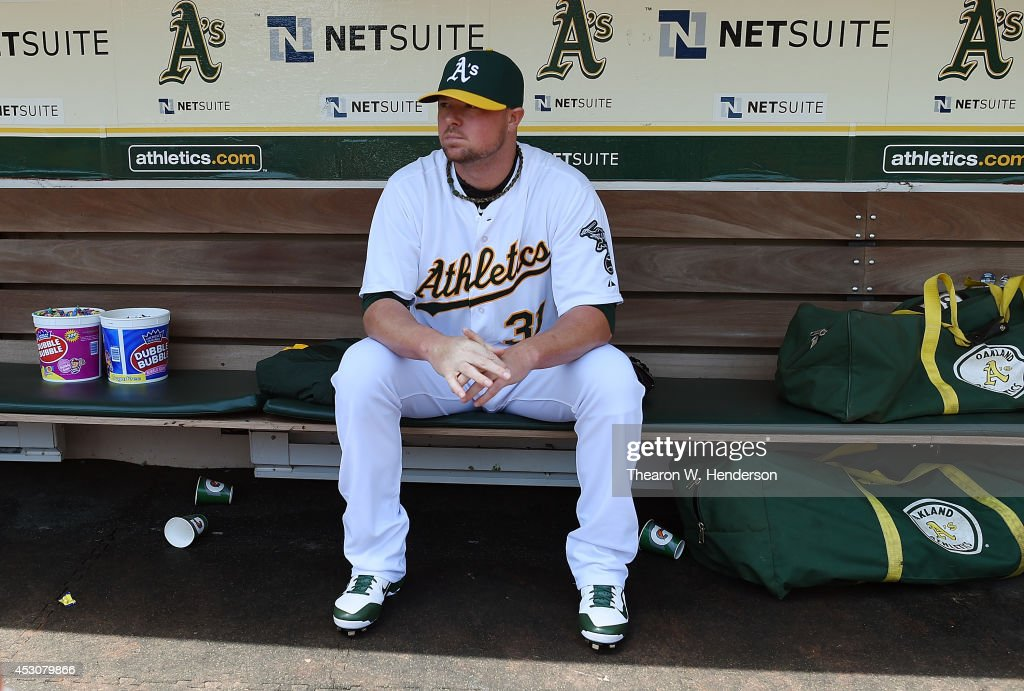Starting pitcher Jon Lester #31 of the Oakland Athletics sits and looks on from the dugout prior to warming up for his start against the Kansas City Royals at O.co Coliseum on August 2, 2014 in Oakland, California.
