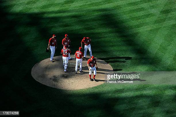 Starting pitcher Jordan Zimmermann of the Washington Nationals reacts as manager Davey Johnson walks to the pitcher's mound to pull him in the sixth...