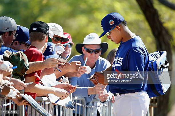 Starting pitcher Julio Urias of the Los Angeles Dodgers signs autographs for fans following a spring training workout at Camelback Ranch on February...