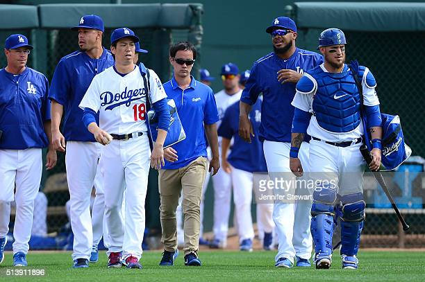 Starting pitcher Kenta Maeda and catcher Yasmani Grandal of the Los Angeles Dodgers take the field prior to the spring training game against the...