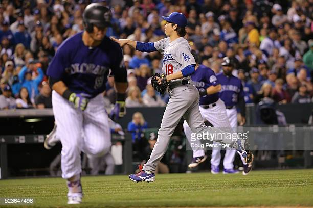 Starting pitcher Kenta Maeda of the Los Angeles Dodgers fields a bases loaded gorund ball by Gerardo Parra of the Colorado Rockies for a force out at...
