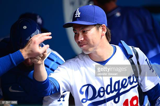 Starting pitcher Kenta Maeda of the Los Angeles Dodgers high fives a teammate prior to the spring training game against the Arizona Diamondbacks at...
