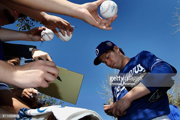 Starting pitcher Kenta Maeda of the Los Angeles Dodgers signs autographs for fans following a spring training workout at Camelback Ranch on February...