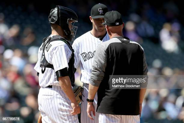 Starting pitcher Kyle Freeland of the Colorado Rockies confers with catcher Dustin Garneau and pitching coach Steve Foster in the first inning...