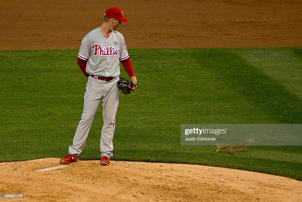 Starting pitcher <a gi-track='captionPersonalityLinkClicked' href=/galleries/search?phrase=Kyle+Kendrick&family=editorial&specificpeople=4365300 ng-click='$event.stopPropagation()'>Kyle Kendrick</a> #38 of the Philadelphia Phillies watches as a squirrel causes a delay in play during the third inning against the Colorado Rockies at Coors Field on April 19, 2014 in Denver, Colorado.