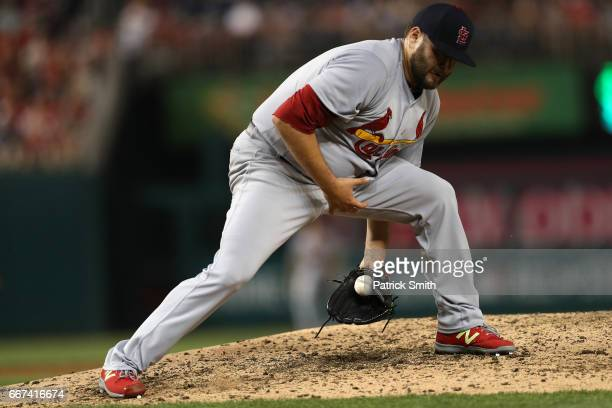 Starting pitcher Lance Lynn of the St Louis Cardinals makes a stop on a hit by Stephen Drew of the Washington Nationals during the fifth inning at...