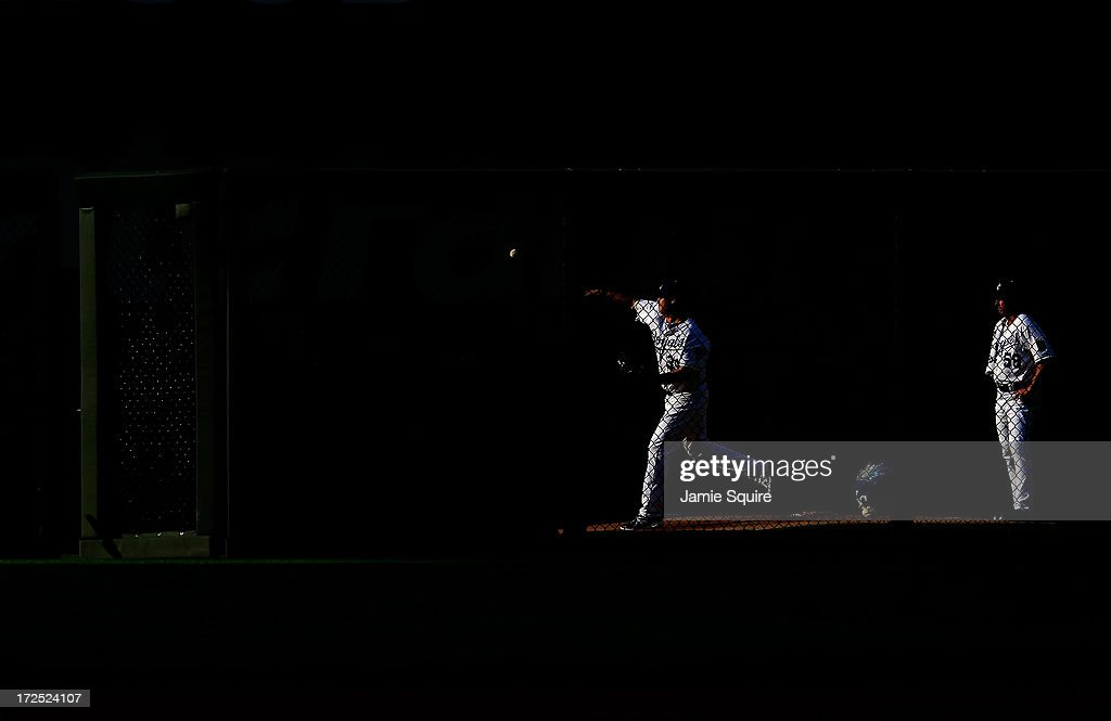 Starting pitcher Luis Mendoza of the Kansas City Royals warms up in the bullpen as pitching coach Dave Eiland looks on prior to the start of the game...