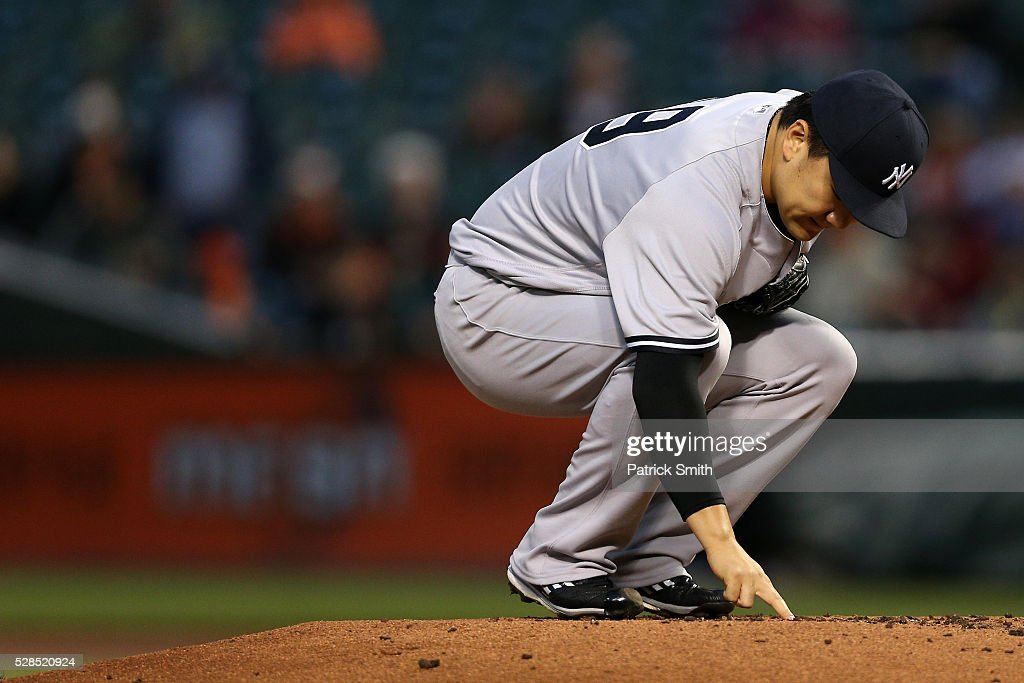 Starting pitcher Masahiro Tanaka #19 of the New York Yankees touches the pitching mound dirt before working the first inning against the Baltimore Orioles at Oriole Park at Camden Yards on May 5, 2016 in Baltimore, Maryland.