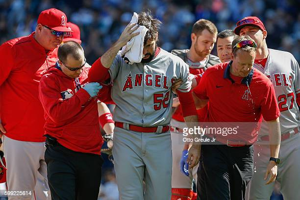Starting pitcher Matt Shoemaker of the Los Angeles Angels of Anaheim is helped off the field after being hit in the head with a batted ball off the...