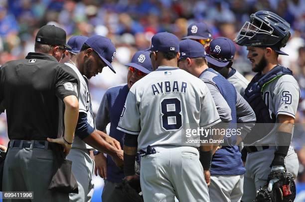 Starting pitcher Miguel Diaz of the San Diego Padres is examined in the 3rd inning after suffering an apparent arm injury against the Chicago Cubs at...