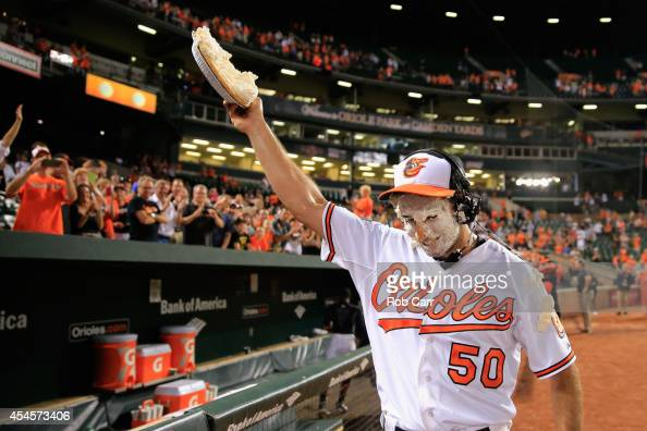 Starting pitcher Miguel Gonzalez of the Baltimore Orioles holds up a pie after getting hit in the face with it from teammate Adam Jones following the...