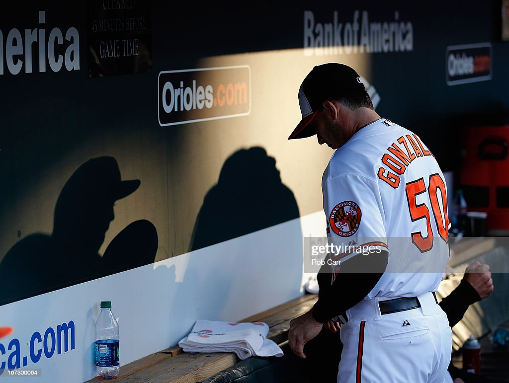 Starting pitcher Miguel Gonzalez #50 of the Baltimore Orioles sits in the dugout before taking the mound against the Toronto Blue Jays at Oriole Park at Camden Yards on April 23, 2013 in Baltimore, Maryland.