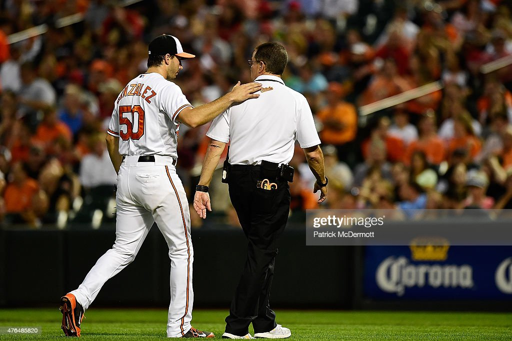 Starting pitcher Miguel Gonzalez #50 of the Baltimore Orioles walks off the field with head athletic trainer Richie Bancells in the top of the fifth inning during a baseball game against the Boston Red Sox at Oriole Park at Camden Yards on June 9, 2015 in Baltimore, Maryland.