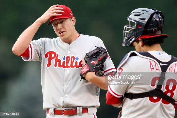 Starting pitcher Nick Pivetta of the Phiadelphia Phillies adjusts his cap while waitng on the mound with catcher Jorge Alfaro for pitching coach Bob...