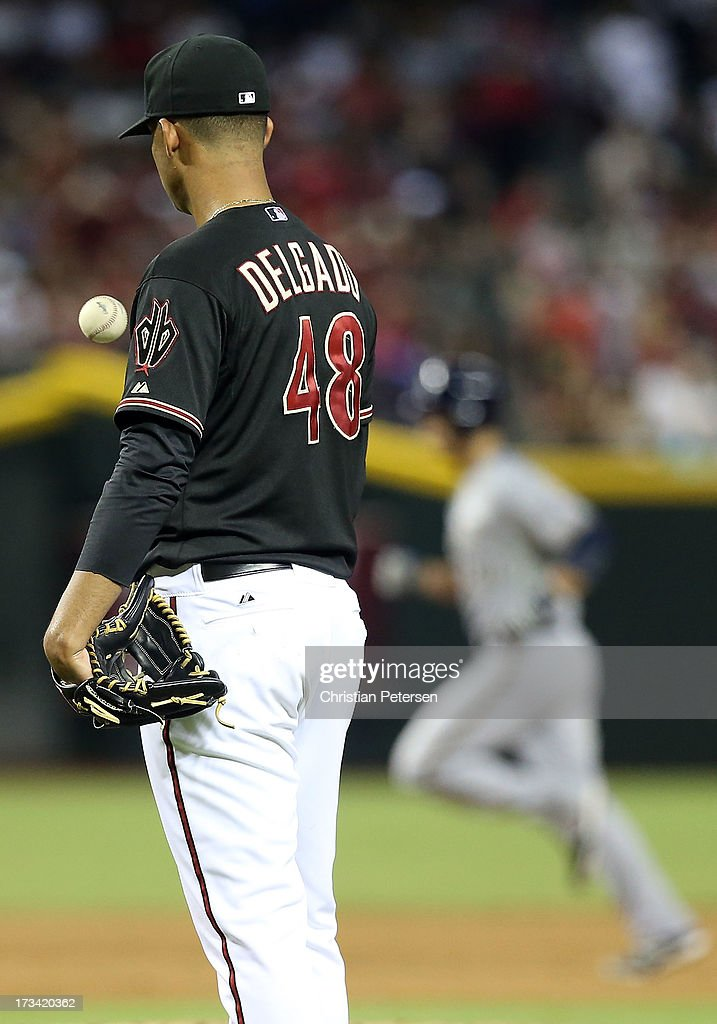 Starting pitcher Randall Delgado #48 of the Arizona Diamondbacks reacts after giving up a two-run home run against <a gi-track='captionPersonalityLinkClicked' href=/galleries/search?phrase=Jonathan+Lucroy&family=editorial&specificpeople=5732413 ng-click='$event.stopPropagation()'>Jonathan Lucroy</a> #20 of the Milwaukee Brewers during the sixth inning of the MLB game at Chase Field on July 13, 2013 in Phoenix, Arizona.
