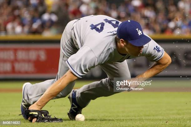 Starting pitcher Rich Hill of the Los Angeles Dodgers falls to the grass after being hit by a line drive single from Paul Goldschmidt of the Arizona...