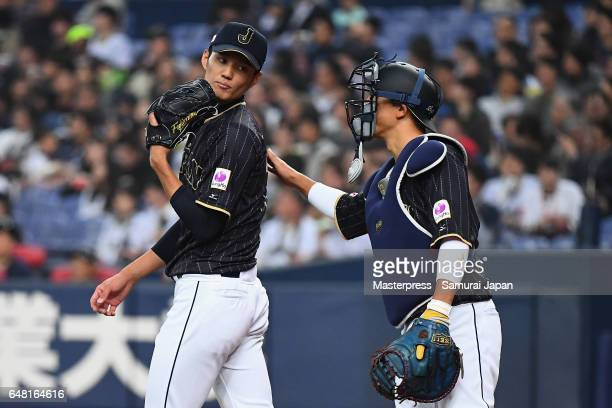 Starting pitcher Shintaro Fujinami of Japan is consoled by Catcher Seiji Kobayashi after allowing a run in the bottom of the first inning during the...