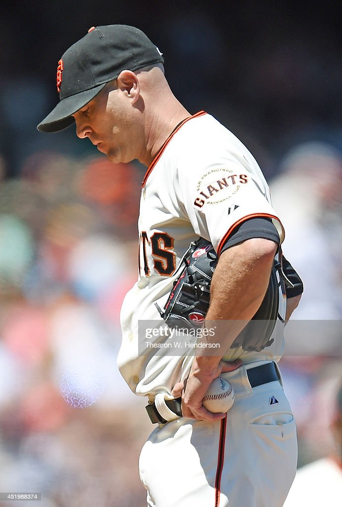 Starting pitcher Tim Hudson #17 of the San Francisco Giants with his hands on his hips waits for manager Bruce Bochy #15 to come take him out of the game in the top of the six inning against the Oakland Athletics at AT&T Park on July 10, 2014 in San Francisco, California.
