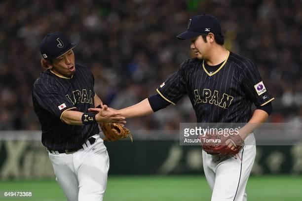 Starting Pitcher Tomoyuki Sugano of Japan high fives with Infielder Nobuhiro Matsuda after the bottom of the third inning during the World Baseball...