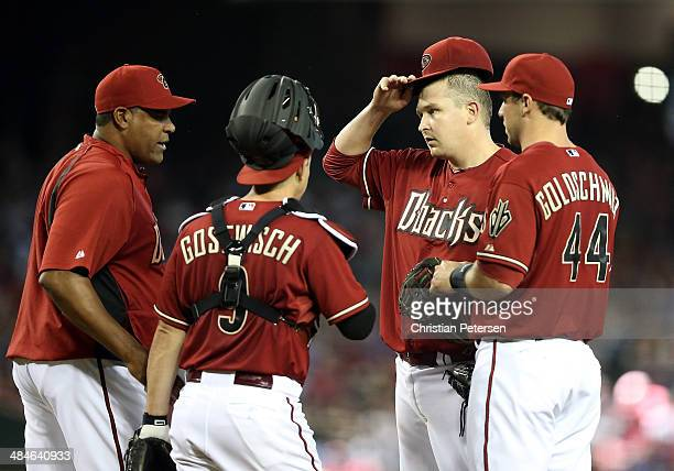 Starting pitcher Trevor Cahill of the Arizona Diamondbacks talks with pitching coach Mike Harkey on the mound during the MLB game against the Los...