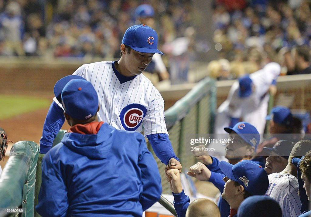 Starting pitcher Tsuyoshi Wada #67 of the Chicago Cubs is congratulated by his teammates after pitching a scoreless fourth inning against the Los Angeles Dodgers at Wrigley Field on September 18, 2014 in Chicago, Illinois.