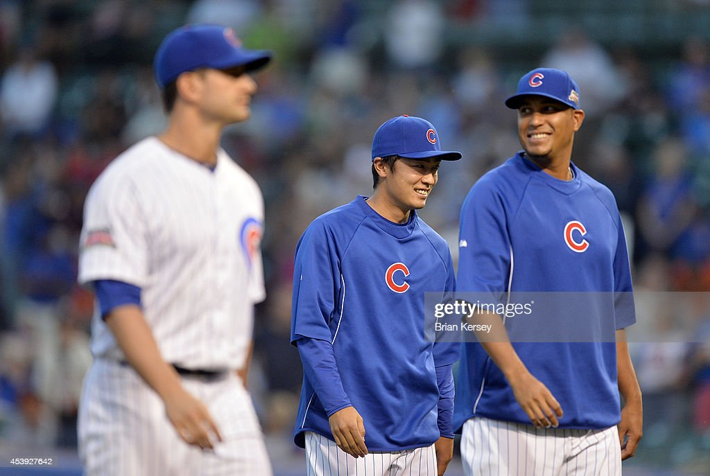 Starting pitcher <a gi-track='captionPersonalityLinkClicked' href=/galleries/search?phrase=Tsuyoshi+Wada&family=editorial&specificpeople=2943743 ng-click='$event.stopPropagation()'>Tsuyoshi Wada</a> #67 of the Chicago Cubs (C) smiles as he walks off the field with his teammates after defeating the San Francisco Giants in a resumed game at Wrigley Field on August 21, 2014 in Chicago, Illinois. The game was initially called off in the early morning hours of August 20 over a protest from the Giants. Major League Baseball accepted the Giants' appeal, ruling the delay was caused by a mechanical failure of the tarp and changing the status of the game from cancelled and completed with a Cubs 2-0 win to a suspended game. The Cubs defeated the Giants 2-1.