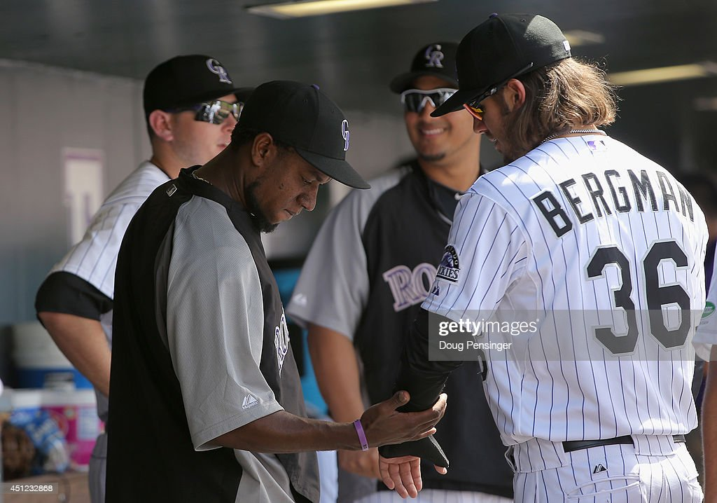 Starting pitcher Yohan Flande #58 of the Colorado Rockies checks out the cast on the broken hand of Christian Bergman #36 of the Colorado Rockies after Flande left the game against the St. Louis Cardinals in his Major League debut at Coors Field on June 25, 2014 in Denver, Colorado. The Cardinals defeated the Rockies 9-6.