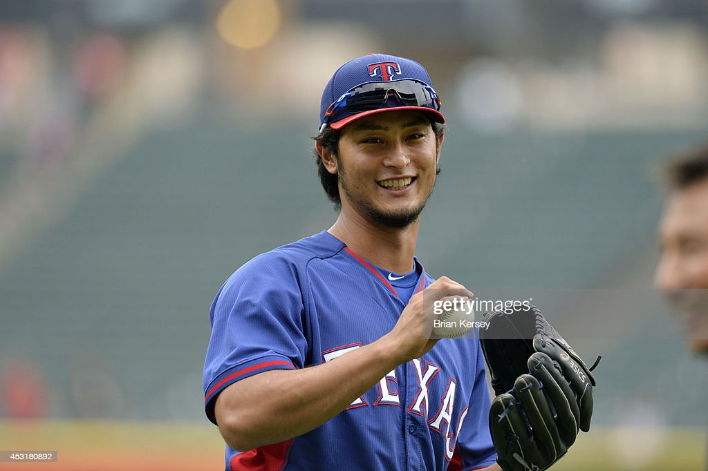 Starting pitcher <a gi-track='captionPersonalityLinkClicked' href=/galleries/search?phrase=Yu+Darvish&family=editorial&specificpeople=4018539 ng-click='$event.stopPropagation()'>Yu Darvish</a> #11 of the Texas Rangers smiles as he plays catch in the outfield during batting practice before the game against the Chicago White Sox at U.S. Cellular Field on August 4, 2014 in Chicago, Illinois.