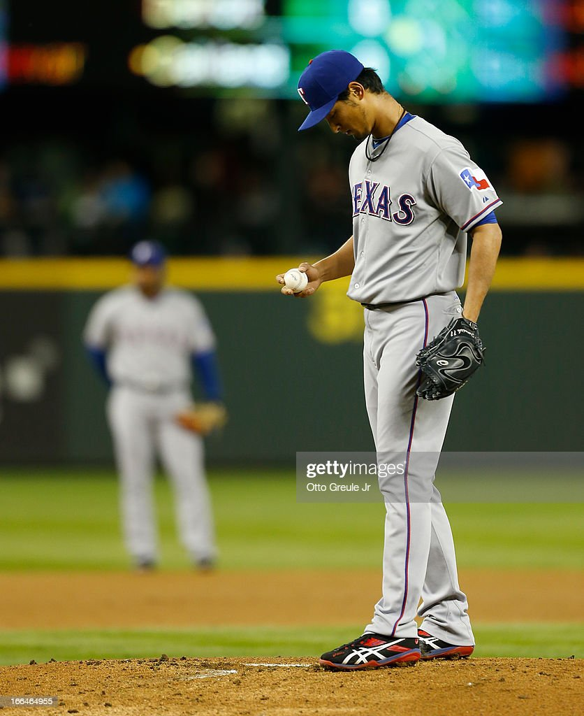 Starting pitcher <a gi-track='captionPersonalityLinkClicked' href=/galleries/search?phrase=Yu+Darvish&family=editorial&specificpeople=4018539 ng-click='$event.stopPropagation()'>Yu Darvish</a> #11 of the Texas Rangers toes the rubber after giving up a two-run double to Kyle Seager of the Seattle Mariners in the first inning at Safeco Field on April 12, 2013 in Seattle, Washington.