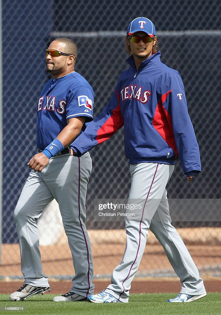 Starting pitcher <a gi-track='captionPersonalityLinkClicked' href=/galleries/search?phrase=Yu+Darvish&family=editorial&specificpeople=4018539 ng-click='$event.stopPropagation()'>Yu Darvish</a> #11 of the Texas Rangers walks onto the field with catcher <a gi-track='captionPersonalityLinkClicked' href=/galleries/search?phrase=Yorvit+Torrealba&family=editorial&specificpeople=212721 ng-click='$event.stopPropagation()'>Yorvit Torrealba</a> #8 during the spring training game against the San Diego Padres at Peoria Stadium on March 7, 2012 in Peoria, Arizona.