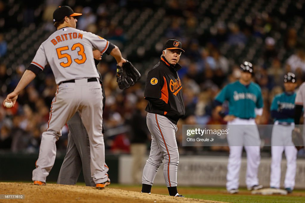 Starting pitcher <a gi-track='captionPersonalityLinkClicked' href=/galleries/search?phrase=Zach+Britton&family=editorial&specificpeople=7091505 ng-click='$event.stopPropagation()'>Zach Britton</a> #53 of the Baltimore Orioles takes a warm-up pitch during an injury delay in the sixth inning as manager <a gi-track='captionPersonalityLinkClicked' href=/galleries/search?phrase=Buck+Showalter&family=editorial&specificpeople=208183 ng-click='$event.stopPropagation()'>Buck Showalter</a> #26 looks on against the Seattle Mariners at Safeco Field on April 29, 2013 in Seattle, Washington.