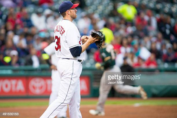 Starting pitcher Zach McAllister of the Cleveland Indians reacts as Josh Reddick of the Oakland Athletics rounds the bases after hitting a grand slam...