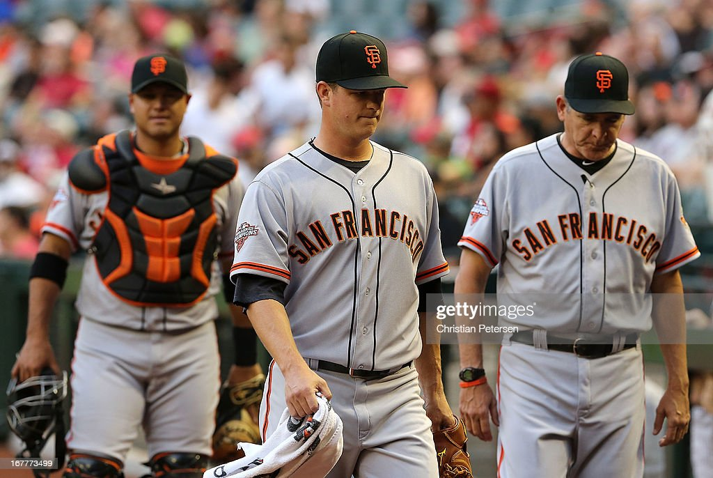 Starting pticher <a gi-track='captionPersonalityLinkClicked' href=/galleries/search?phrase=Matt+Cain&family=editorial&specificpeople=534602 ng-click='$event.stopPropagation()'>Matt Cain</a> #18 (C) of the San Francisco Giants walks to the dugout before the MLB game against the Arizona Diamondbacks at Chase Field on April 29, 2013 in Phoenix, Arizona.