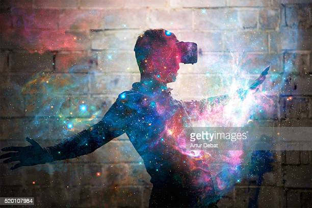 Startled guy interact with virtual reality headsets inside a decay and dark warehouse transported to outer space.