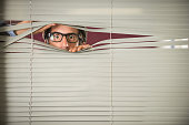 Nerdy startled man in glasses, mid thirties, staring through Venetian blinds.