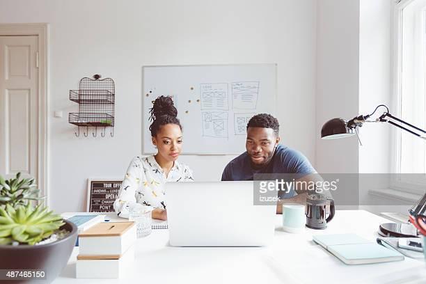 Start-up agenzia, afro-americana donna e uomo collaborare