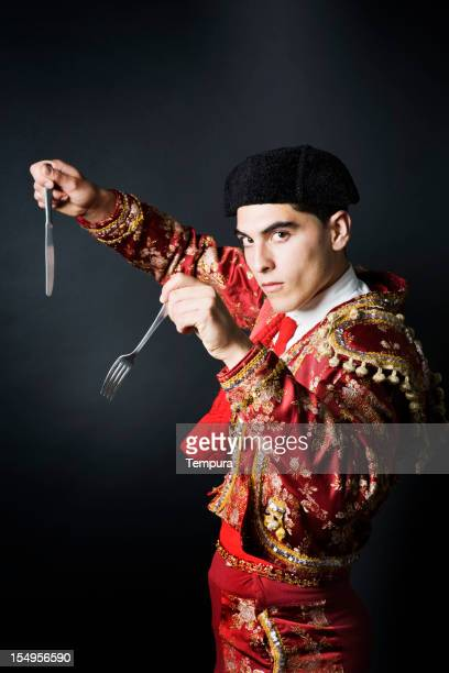 Starving spanish bull fighter with knife and fork